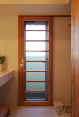 尼崎T邸。玄関と洗面の勝手口に設けたアウトセット引戸タイプの造作網戸。視線がないので格子は荒め。