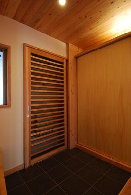 伊丹O邸。壁と玄関収納の間に引き込まれる造作網戸。廊下を通る人が多いので格子は細かめにした。