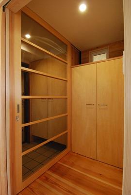 三田F邸。玄関ドアから1000ミリほどセットバックした位置に設けた引込みの造作網戸。