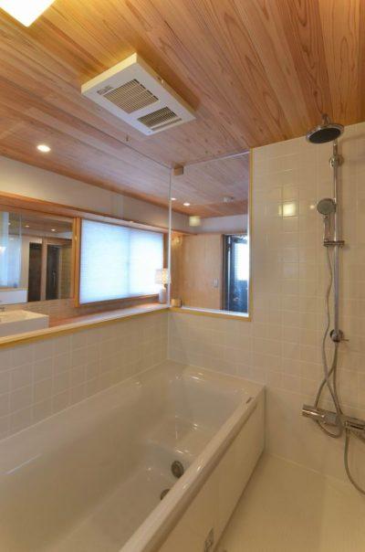 壁はタイル、天井を木としてガラス張りで仕上げたハーフユニットバスの事例